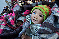 A young boy rides in a basket on his father's back in the Kargil District of Ladakh, India.
