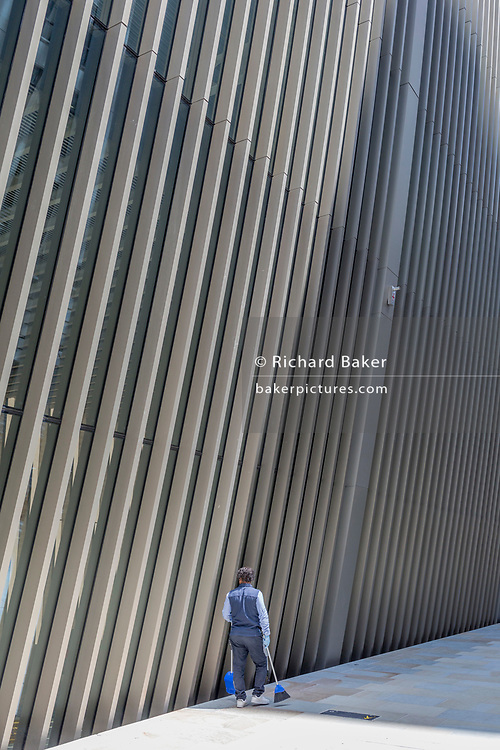 Beneath new architecture, a City worker carrying a dustpan and brush walks along Bevis Marks in the City of London, the capital's financial district, on 17th June 2019, in London, England.
