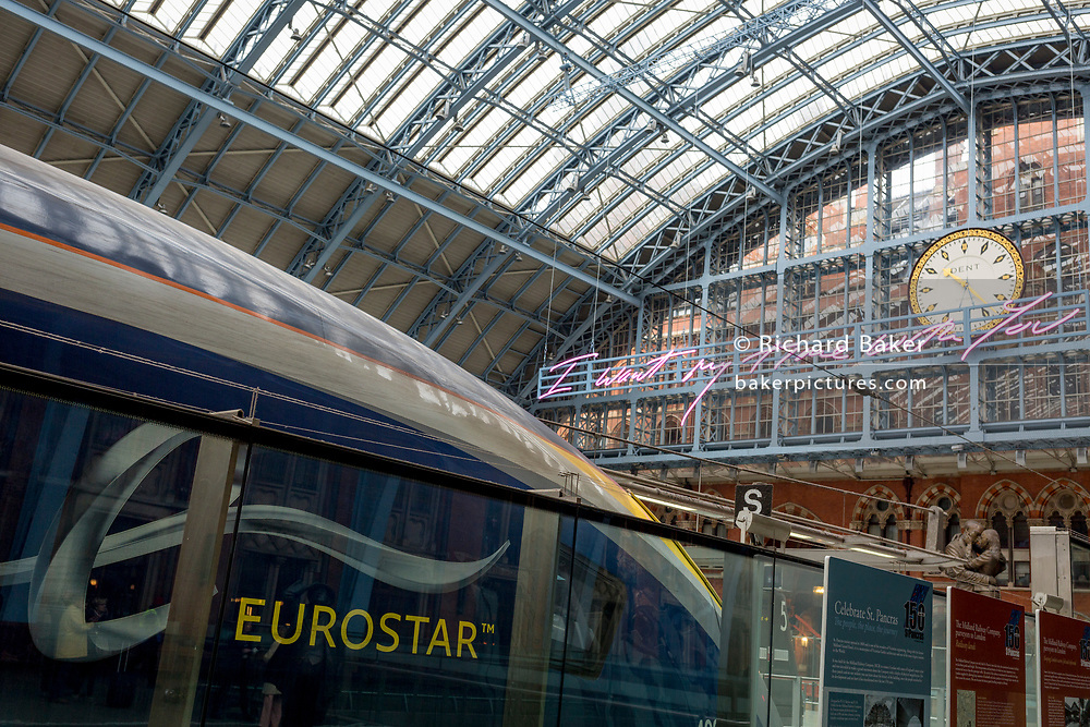"""A Eurostar train and the new artwork entitled 'I Want My Time With You' by British (Britpop) artist Tracy Emin hangs over the main concourse at St. Pancras Station, on 10th April 2018, in London, England. In the sixth year of the Terrace Wires Commission - and in celebration of the 150th anniversary of St Pancras International and the 250th anniversary of the Royal Academy of Arts, at one of London's mainline station, the London hub for Eurostar - the 20 metre-long greeting to commuters reads 'I Want My Time With You' and Emin thinks that arriving by train and being met by a lover as they put their arms around them, is very romantic."""" The Brexit-opposing artist also said she wanted to make """"a statement that reaches out to everybody from Europe arriving in to London""""."""
