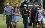 Cheer up, guys! The Obamas look downcast as they return home from two-week break on Martha's Vineyard<br /> <br /> President Obama and the first family looked glum when they stepped off Marine One outside of the White House after their summer vacation.<br /> They had been on Martha's Vineyard for the past two weeks, enjoying their annual summer break - and they seemed far from happy to be home. <br /> En route to the capital on Sunday, they stopped off at Cape Cod to swap their first helicopter for the President's plane Air Force One, and they managed to smile at crowds on the tarmac. <br /> But as the family disembarked Air Force One at Andrews Air Force base, before taking another helicopter back to their official residence, the happy faces had vanished.<br /> At the White House, a serious-looking Obama took the hand of his 17-year-old daughter Malia, while his wife and Sasha, 14, followed behind.  <br /> ©Exclusivepix Media