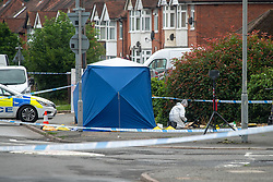 CAPTION UPDATE © Licensed to London News Pictures. 31/07/2021. High Wycombe, UK. A forensic investigator gathers evidence next to a large police tent as a murder investigation is launched in High Wycombe following the discovery by a police patrol of a person on the ground at approximately 12:20BST surrounded by a group of males who fled the scene when the police officers arrived, despite the efforts of police and paramedics the man died at the scene. Photo credit: Peter Manning/LNP