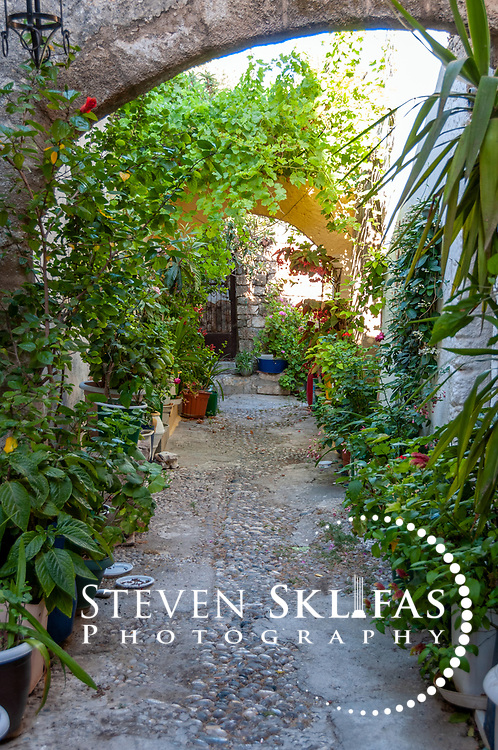 Rhodes. Greece. Arched pebbly private garden with colourful flowers green plants inside the old walled medieval town of Rhodes. The old town is a UNESCO world heritage listed site and the best preserved, oldest and largest living medieval city in Europe.