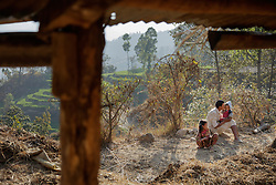 """Durga kisses his youngest daughter, 11-month-old Kusum, while Sumitra, 10, sits nearby. """"Of all our children, he loves her the most,"""" Niruta said of Durga and the baby. Durga wants her to become a doctor. <br /> <br /> Niruta and Durga were married 9 years ago, when they were just 14 and 16 years old in the Kagati village of Nepal. The 2015 earthquakes devastated Nepal and left girls and women in an increasingly vulnerable position, leading experts to believe child marriage rates will increase over the coming years."""