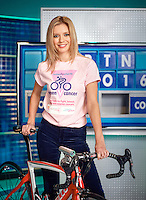 Rachel Riley photographed on on the Countdown TV set in front of letters board. Rachel Riley is wearing a woman against Cancer T Shirt and is leaning over a professional racing cycle