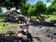 """22 JANUARY 2018 - CAMALIG, ALBAY, PHILIPPINES: A family carries their belongings to a waiting government truck after they were told they had to evacuate their home because of its proximity to the Mayon volcano. There were a series of eruptions on the Mayon volcano near Legazpi Monday. The eruptions started Sunday night and continued through the day. At about midday the volcano sent a plume of ash and smoke towering over Camalig, the largest municipality near the volcano. The Philippine Institute of Volcanology and Seismology (PHIVOLCS) extended the six kilometer danger zone to eight kilometers and raised the alert level from three to four. This is the first time the alert level has been at four since 2009. A level four alert means a """"Hazardous Eruption is Imminent"""" and there is """"intense unrest"""" in the volcano. The Mayon volcano is the most active volcano in the Philippines. Sunday and Monday's eruptions caused ash falls in several communities but there were no known injuries.    PHOTO BY JACK KURTZ"""