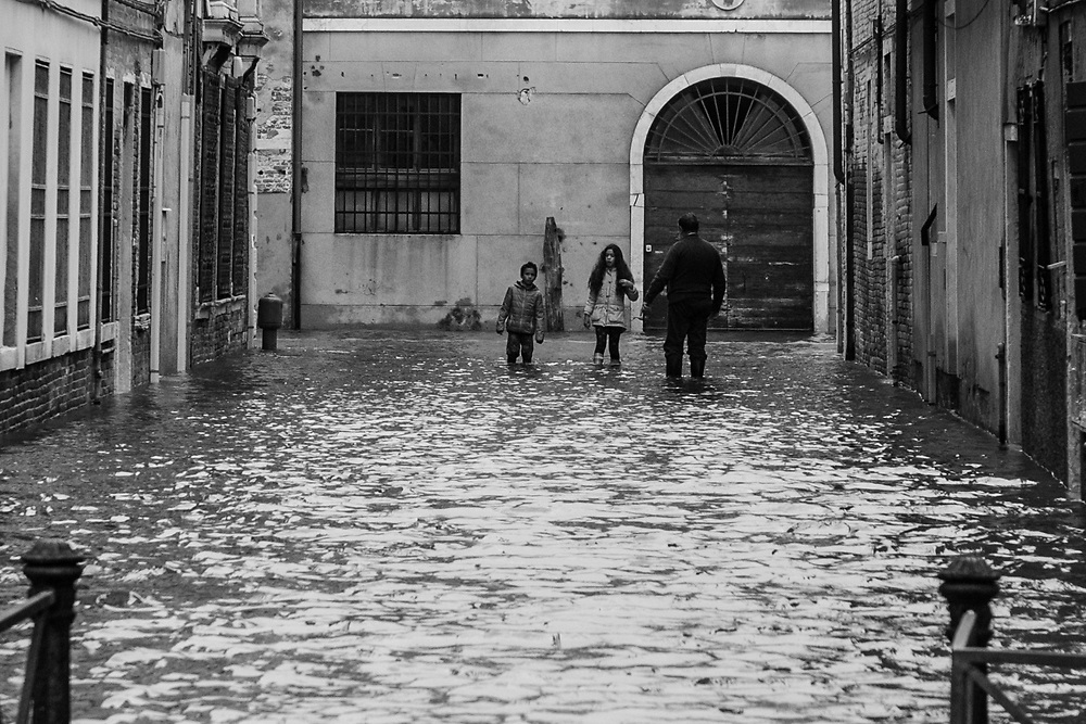 Venice, Italy. 29 October, 2018. Children walk during the high tide in Cannaregio district on October 29, 2018, in Venice, Italy. This is a selection of pictures of different areas of Venice that the press has not covered, were resident live and every year they have to struggle with the high tide. Due to the exceptional level of the 'acqua alta' or 'High Tide' that reached 156 cm today, Venetian schools and hospitals were closed by the authorities, and citizens were advised against leaving their homes. This level of High Tide has been reached in 1979. © Simone Padovani / Awakening / Alamy Live News