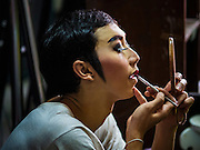 """30 JANUARY 2016 - NONTHABURI, NONTHABURI, THAILAND: A performer puts on his makeup before a """"likay"""" show at Wat Bua Khwan in Nonthaburi, north of Bangkok. Likay is a form of popular folk theatre that includes exposition, singing and dancing in Thailand. It uses a combination of extravagant costumes and minimally equipped stages. Intentionally vague storylines means performances rely on actors' skills of improvisation. Like better the known Chinese Opera, which it resembles, Likay is performed mostly at temple fairs and privately sponsored events, especially in rural areas. Likay operas are televised and there is a market for bootleg likay videos and live performance of likay is becoming more rare.     PHOTO BY JACK KURTZ"""