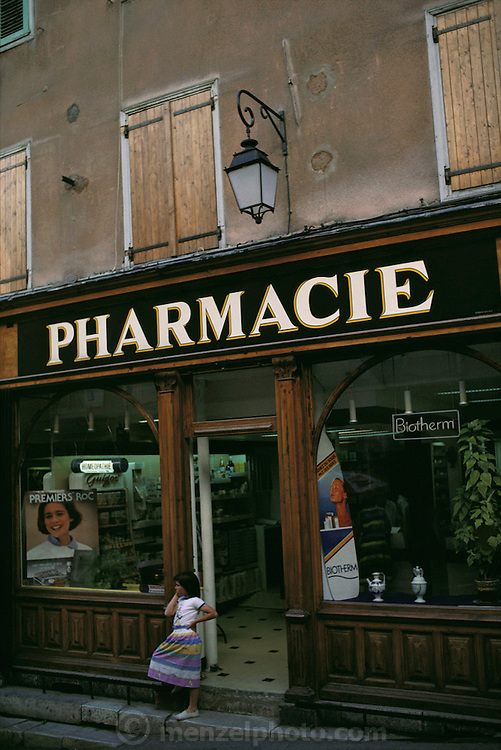 Pharmacy with a young girl waiting in the doorway. Briancon, France.
