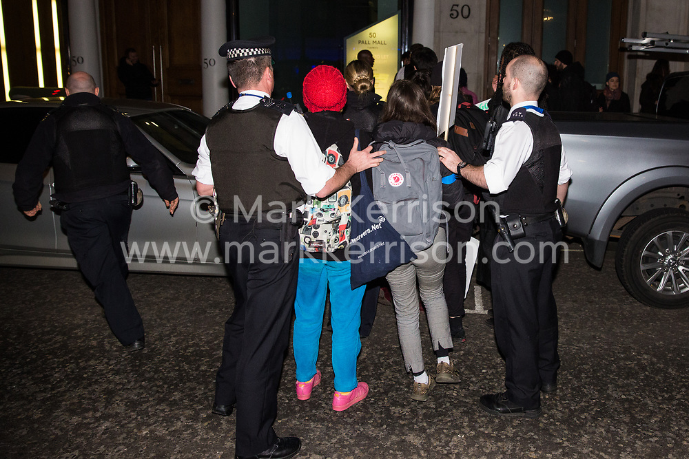 London, UK. 12th February, 2019. Police officers push members of grassroots trade union United Voices of the World out of the road during a protest outside the Gadson Club in Pall Mall on the occasion of a reception with Justice Secretary David Gauke against his refusal to negotiate with the trade union over their demands for the London Living Wage, annual leave and sick pay for outsourced cleaners, security guards and receptionists working at the Ministry of Justice, all of whom have been on strike for varying periods recently. The Gadson Club is the official alumni club for the Oxford University Conservative Association.