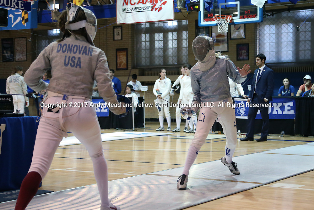 12 February 2017: Duke's Lindsay Sapienza (right) lunges at Boston College's Laura Donovan (left) during Saber. The Duke University Blue Devils hosted the Boston College Eagles at Card Gym in Durham, North Carolina in a 2017 College Women's Fencing match. Duke won the dual match 19-8 overall, 6-3 Foil, 5-4 Epee, and 8-1 Saber.