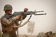 An Afghan National Army machinegunner shoots at Afghan insurgent positions.