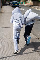 Two children running away down a street,
