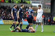 Swansea city's Michu has words with Tottenham players after he collides with Tottenham's Scott Parker on ground and is booked for this challenge by ref Anthony Taylor. Barclays Premier League, Swansea city v Tottenham Hotspur at the Liberty Stadium in Swansea, South Wales on Saturday 30th March 2013. pic by Andrew Orchard, Andrew Orchard sports photography,