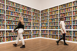 "© Licensed to London News Pictures. 08/04/2019. LONDON, UK.  Staff members walk by British-Nigerian artist Yinka Shonibare's artwork ""The British Library"", 2014, which has been acquired by Tate Modern.  Comprising 6,328 books, covered in wax fabric and gold foil, 2,700 books have the names of first or second generation immigrants to Britain on the spine.  Photo credit: Stephen Chung/LNP"