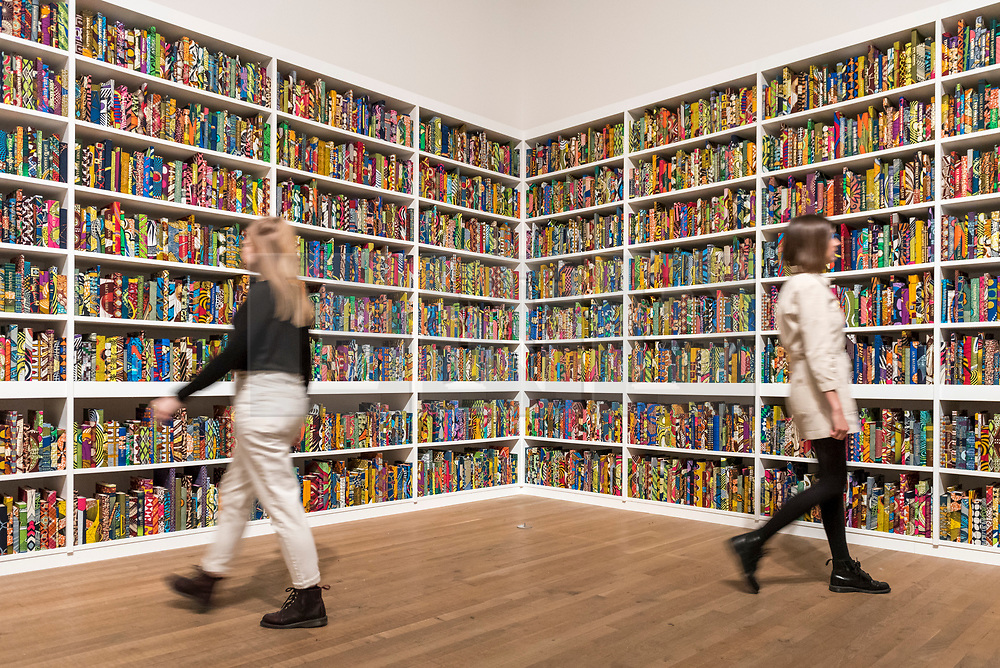"""© Licensed to London News Pictures. 08/04/2019. LONDON, UK.  Staff members walk by British-Nigerian artist Yinka Shonibare's artwork """"The British Library"""", 2014, which has been acquired by Tate Modern.  Comprising 6,328 books, covered in wax fabric and gold foil, 2,700 books have the names of first or second generation immigrants to Britain on the spine.  Photo credit: Stephen Chung/LNP"""