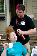 Woman enjoying cup of beer while beautician creates her buzz style in outdoor beauty shop. Grand Old Day St Paul Minnesota USA