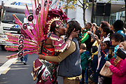 Hackney carnival 2014. The procession started in Ridley Road and passed by the The Hackney Town Hall with thousands of spectators lining the road. A female dancer kisses and greets a friend along the the way passing the Town Hall.