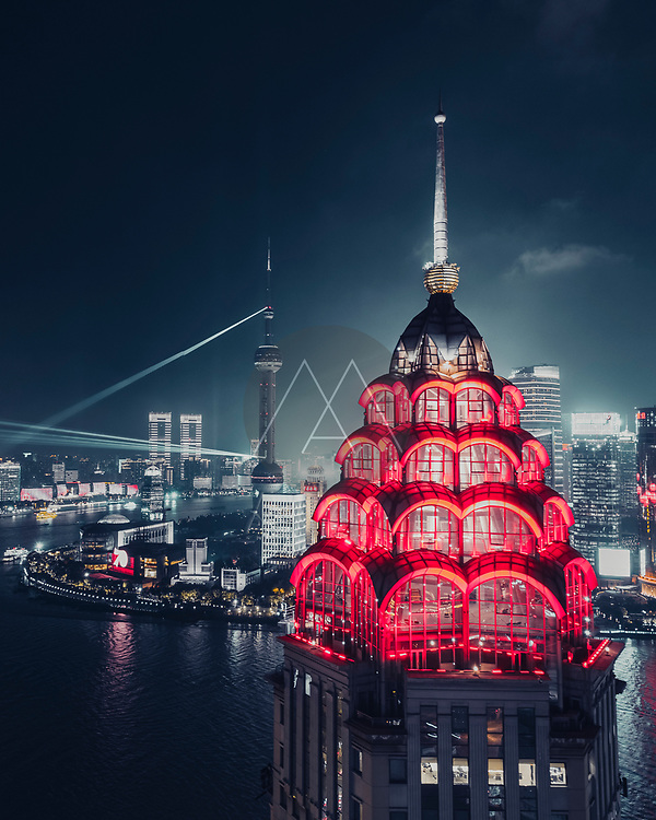 Shanghai, China - 29 September 2019: Aerial view of the top of a skyscraper illuminated with red lights and Shanghai skyline in background, Shanghai, China.