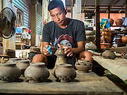 29 AUGUST 2105 - KO KRET, NONTHABURI, THAILAND: A man works in a pottery factory on Ko Kret. Ko Kret is a small island in the Chao Phraya River in Nonthaburi province north of Bangkok. It is some 2 km long and 1 km wide. It has seven main villages, the largest and most populous being Ban Mon. Ko Kret was created in 1722 when a canal was dug in the Chao Phraya River to bypass a bend. Most of the people on the island are ethnically Mon, from the hills of western Thailand and eastern Myanmar (Burma). The island is popular as a weekend daytrip from Bangkok. The island is famous for the Mon style pottery made on the island.   PHOTO BY JACK KURTZ