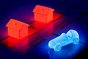 A glowing car and hotel pieces on a Monopoly game board.<br />Blacklight Photography