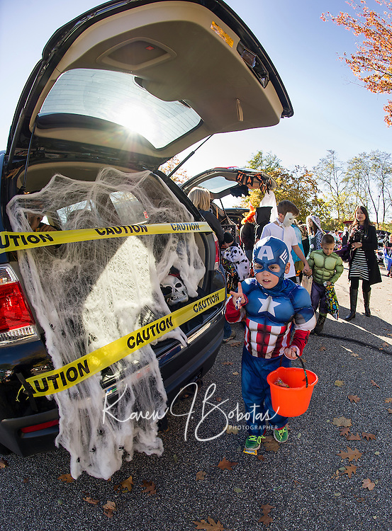 """Chael Smithson """"Captian America"""" makes off with a treat from the trunk of Bryan Holland's """"Spiders and Skulls"""" mobile during Holy Trinity School's Trunk or Treat on Monday afternoon.  (Karen Bobotas/for the Laconia Daily Sun)"""