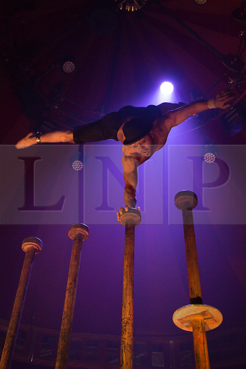"""© Licensed to London News Pictures. 15/05/2013. London, England. Picture: Danik Abishev performs a hand balancing act on high poles. Creators of the critically-acclaimed """"Cantina"""" return to London this summer (10 May to 29 September) with their new show """"Limbo"""" at London Wonderground/Southbank Centre. London Wonderground headline act """"Limbo"""" is a mix of cabaret, circus and acrobatics.  Photo credit: Bettina Strenske/LNP"""