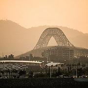 The setting sun catches the haze looking towards the Bridge of Americans across the Panama Canal in Panama City, Panama.