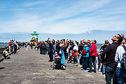 Visitors of Volvo Ocean Race event looking at a low flying helicopter.