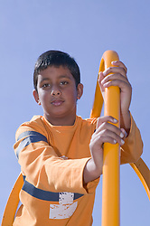 Young boy playing on a climbing frame in a playground,