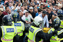 © Licensed to London News Pictures. 09/06/2018. London, UK. Supporters of EDL founder Tommy Robinson ( real name Stephen Yaxley-Lennon ) clash with police in Trafalgar Square during a demonstration on Whitehall in Westminster after Robinson was convicted of Contempt of Court . Robinson was already serving a suspended sentence for Contempt of Court over a similar incident , when he was convicted on Friday 25th May 2018 . Photo credit: Joel Goodman/LNP