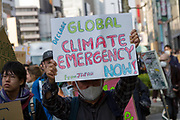 """An older man holds a sign as he joins young  people taking part in the Global Strike for Future at the United Nations University, Shibuya, Tokyo, Japan.Friday March 15th 2019. Part of a global day of action in 98 countries and nearly 2,000 cities; this was Japan's second Fridays for Future event, known as """"School strikes"""", and took place from 2pm to 4pm with activists and students holding signs demanding leaders, internationally and nationally, take measures to reduce ecologically damaging activities. The movement was started in 2018 by Swedish schoolgirl, Greta Thunberg, who began striking from her lessons when she realised that adult leaders were doing nothing to ensure there would be the future she was studying for."""