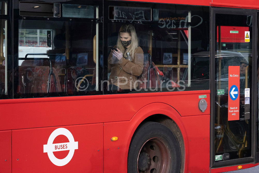 Young woman on a bus looks closely at her smart phone as the national coronavirus lockdown three continues on 5th March 2021 in London, United Kingdom. Public transport use is still low amongst the public, with all transport for London services aiming to limit numbers. With the roadmap for coming out of the lockdown has been laid out, this nationwide lockdown continues to advise all citizens to follow the message to stay at home, protect the NHS and save lives, and the streets of the capital are quiet and empty of normal numbers of people.