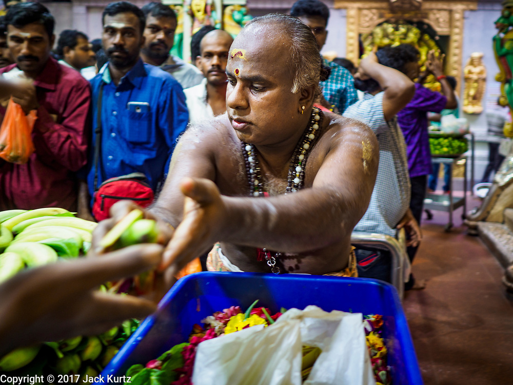 """09 JULY 2017 - SINGAPORE:  A Hindu priest hands out bananas that have been blessed in Sri Veeramakaliamman Temple in Singapore's """"Little India."""" There are hundreds of thousands of guest workers from the Indian sub-continent in Singapore. Most work 5 ½ to six days per week. On Sundays, the normal day off, they come into Singapore's """"Little India"""" neighborhood to eat, drink, send money home, go to doctors and dentists and socialize. Most of the workers live in dormitory style housing far from central Singapore and Sunday is the only day they have away from their job sites. Most work in blue collar fields, like construction or as laborers.   PHOTO BY JACK KURTZ"""
