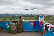 A Nepalese woman hangs out washing on the balcony of the Friends of Needy Children Nutritional Rehabilitation Centre, Kathmandu, Nepal.  She has attended the centre because one of her children is malnourished and needed healthcare intervention. The centre overlooks the outskirts of Kathmandu and the surrounding valley mountain range.