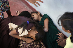 "Shrianna Barthelot, 11, in green dress, plays dead during a game of ""tsunami"" with friends, Batticaloa, Sri Lanka, Jan. 28, 2005. She and her sister Brianna, 13, not pictured here, lost both parents and their older brother in the tsunami. They are now living with relatives at night and spending most of their days at the convent where the rest of their village is staying. Residents of the small Christian village Dutch Bar spent more than six weeks in a makeshift refugee camp at the local convent recovering from the devastating tsunami that hit the eastern and southern borders of Sri Lanka. They were then moved into another temporary living camp, while awaiting the building of new homes. More than 150 members in this community of less than 1000 people died in the tragic event."