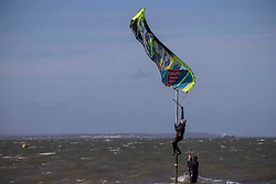© Licensed to London News Pictures.27/03/2021. Southend-On-Sea,UK. A kitesurfer trys to unhook his kite from the information sign at the Thames Estuary in Southend-on-Sea, Essex. The weather forecasts predict sunny weather with strong winds in the southeast England.`Photo credit: Marcin Nowak/LNP