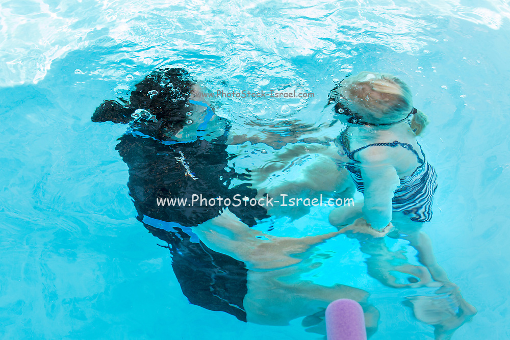 mother and daughter swim together underwater in a swimming pool