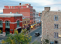 The view from a bridge into Old Quebec City and the historic street of Rue St. Jean shows the early European architecture of the colorful rowhouses and businesses below.