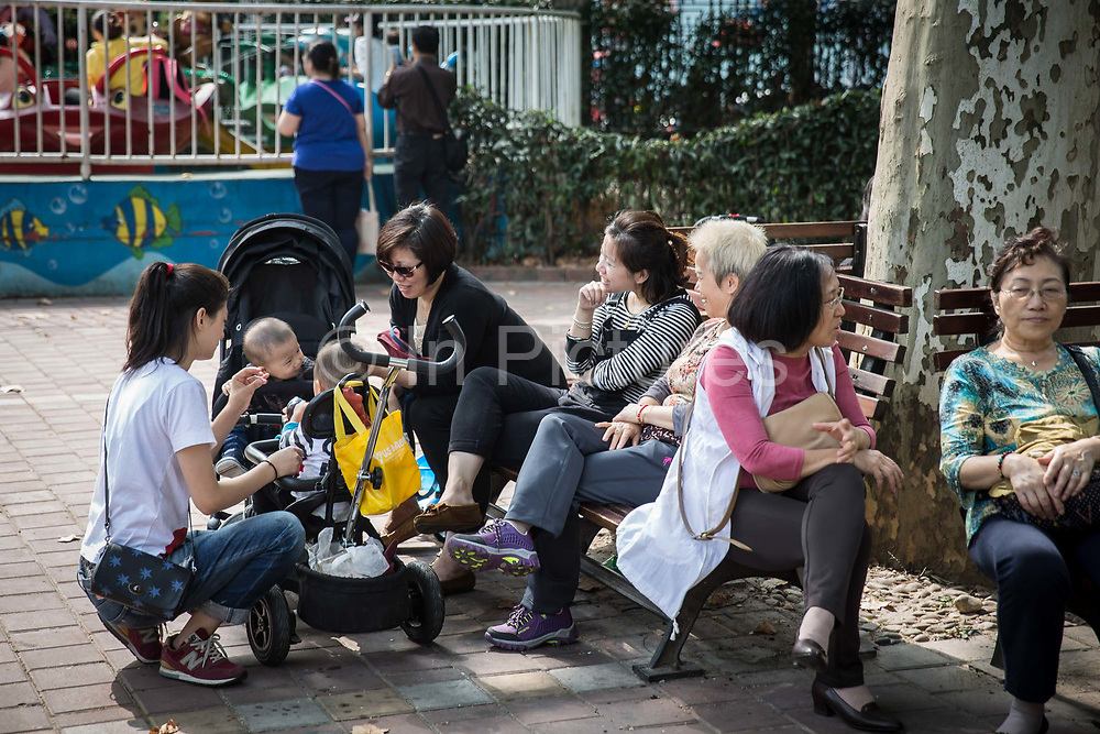 Families take a seat under the sun to enjoy the warm weather at Lu Xun Park in Shanghai, China, on Saturday, Oct. 24, 2015.