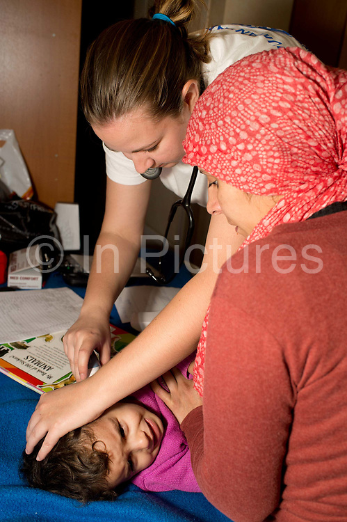 Greece . Hellenic Seaways ferry from Lesvos to Chios to Athens, taken by refugees. Doctors of the World have a clinic on board with a doctor, nurse, interpreters and social workers. Dr Kerry Pritchard examines a little girl.