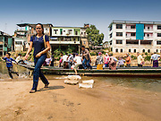 """01 MARCH 2014 - MAE SOT, TAK, THAILAND: Burmese passengers get off a boat at a boat landing in the Moie River in Mae Sot. Boats from Myawaddy, Myanmar (the buildings in the background are in Myawaddy) drop and pick up passengers for the short trip across the river. Mae Sot, on the Thai-Myanmar (Burma) border, has a very large population of Burmese migrants. Some are refugees who left Myanmar to escape civil unrest and political persecution, others are """"economic refugees"""" who came to Thailand looking for work and better opportunities.    PHOTO BY JACK KURTZ"""