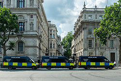 © Licensed to London News Pictures. 19/07/2021. LONDON, UK.  A line of police vehicles outside Downing Street as people take part in an anti-vaccine protest in Parliament Square, on what has been dubbed Freedom Day, when the UK government relaxed remaining coronavirus lockdown restrictions but the numbers of positive cases continues to increase daily and scientists concerned that restrictions have been eased too soon.  Photo credit: Stephen Chung/LNP