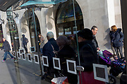 Londoners wait for the next bus service at a bus stop in Kingston town centre, on 13th November 2019, in London, England.