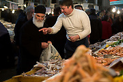 A Greek Orthodox priest  buys seafood from a stall in the Athens Central Market on Athinas Street. Athens, Greece