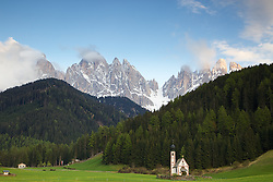 Church at Val di Funnes in Dolomite Mountains, South Tyrol, Italy. The jagged peaks of the Olde Range tower over the valley.