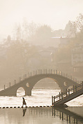 View of a traditional Chinese style arch bridge across a river and an old town in the background, Fenghuang, Hunan Province, China