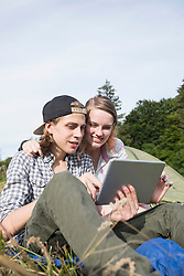 Young couple using digital tablet in front of camp tent, Bavaria, Germany