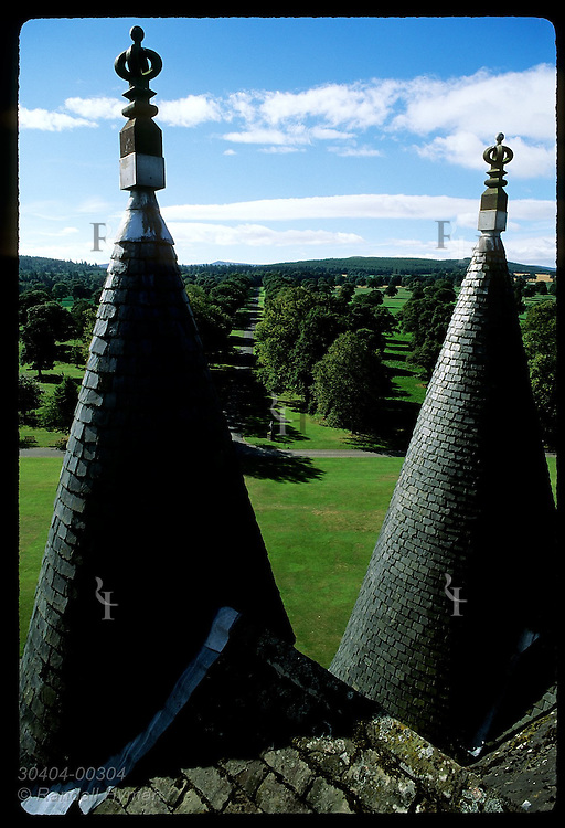 View of Glamis estate from roof of Glamis Castle, childhood home of Queen Mother, framed by castle turrets; Glamis, Scotland.