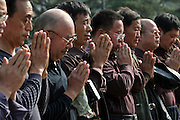 SHAOSHAN, CHINA - 4 NOVEMBER 2005 - A tour group prays in front of Mao's statue by bringing their hands together and kowtowing three times - a ritual that in ancient, feudal China was reserved for the emperor alone. Though even state media today continues to remind people that Mao was just a man and not a god, here the admonishment seems to fall on deaf ears. Photo by Natalie Behring