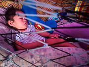 26 JANUARY 2018 - SANTO DOMINGO, ALBAY, PHILIPPINES: A child sleeps in the temporary shelter her parents built in a field in Santo Domingo. The family lives on the slopes of the Mayon volcano and was evacuated because of the volcano's recent eruptions. The volcano was relatively quiet Friday, but the number of evacuees swelled to nearly 80,000 as people left the side of  the volcano in search of safety. There are nearly 12,000 evacuees in Santo Domingo, one of the communities most impacted by the volcano. The number of evacuees is impacting the availability of shelter space. Many people in Santo Domingo, on the north side of the volcano, are sleeping in huts made from bamboo and plastic sheeting. The Philippines is now preparing to house the volcano evacuees for up to three months.       PHOTO BY JACK KURTZ